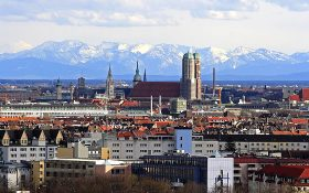 An aerial view of Munich with mountains in the background